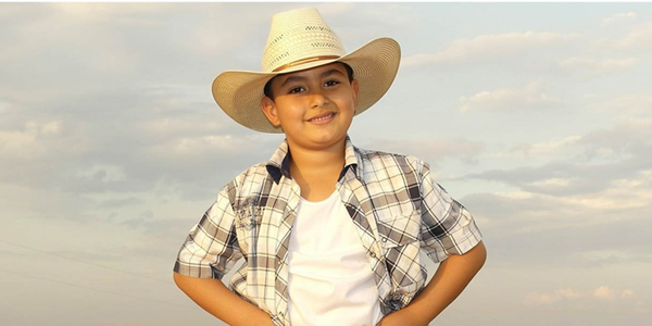 Young boy wearing a cowboy hat.