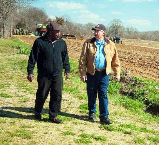 Two farmers walking along a field